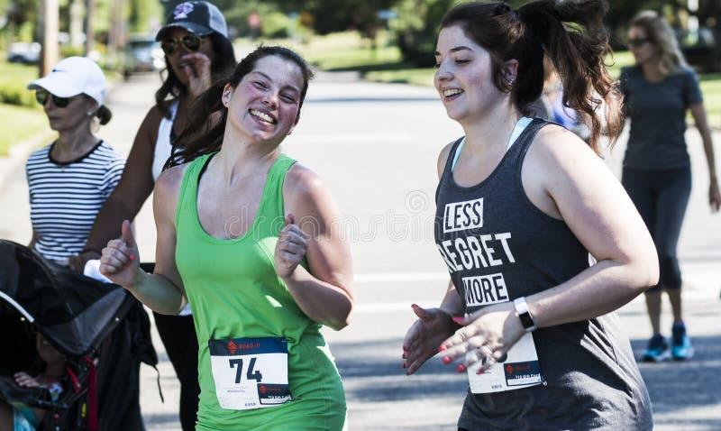 Las mujeres jovenes sonríen en la cámara en el ciclismo en ruta 5K imagen de archivo
