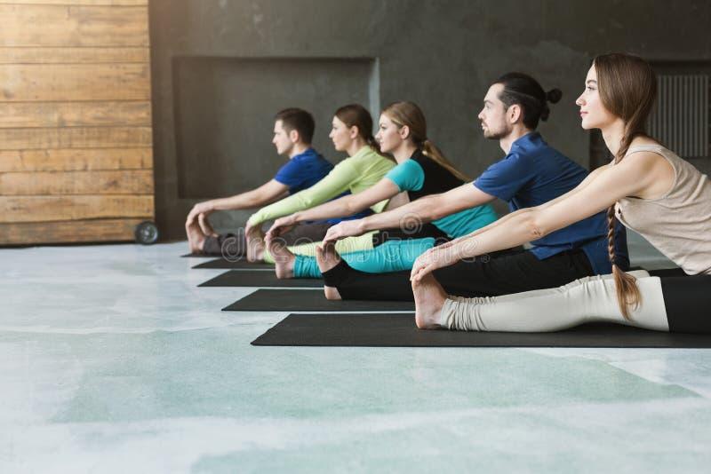 Las mujeres jovenes y los hombres en yoga clasifican, haciendo estirando ejercicios foto de archivo