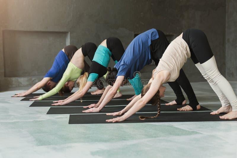 Las mujeres jovenes y los hombres en yoga clasifican, haciendo estirando ejercicios imágenes de archivo libres de regalías