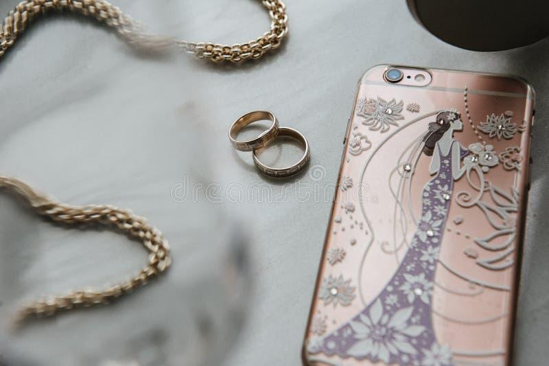 Las mujeres \ los 'accesorios de s están en la tabla La cadena, teléfono, anillos está en la tabla foto de archivo libre de regalías