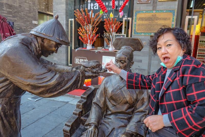 Las mujeres mayores divertidas intentan robar un poco de comida de la estatua del pueblo chino dan su comida a las mujeres en la  fotografía de archivo