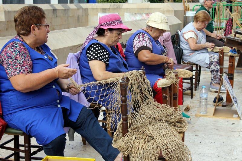 Las mujeres mayores son de trabajo y de fabricación de objetos con los materiales de esparto y del cáñamo de la hierba foto de archivo libre de regalías