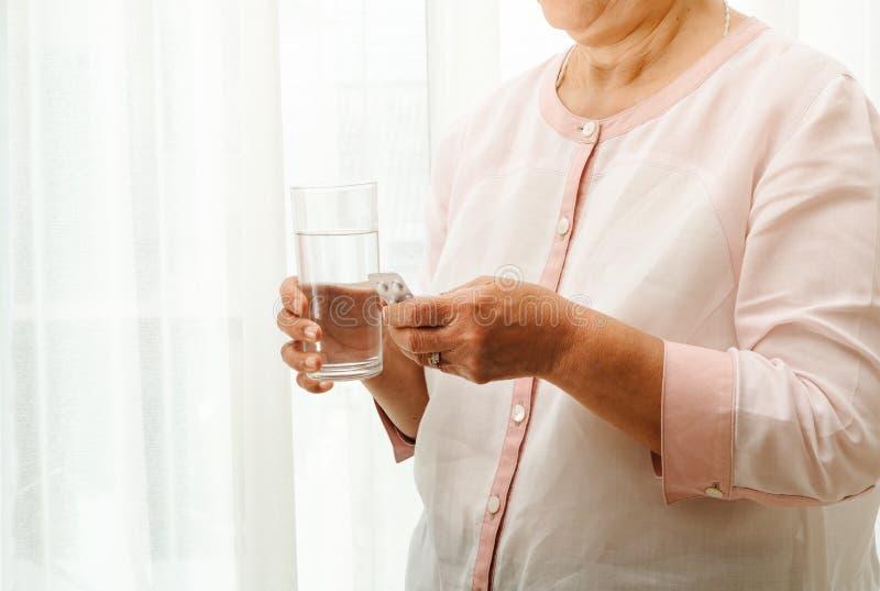 Las mujeres mayores toman la medicina con un concepto de la recuperación del vaso de agua, de la atención sanitaria y de la medic fotografía de archivo