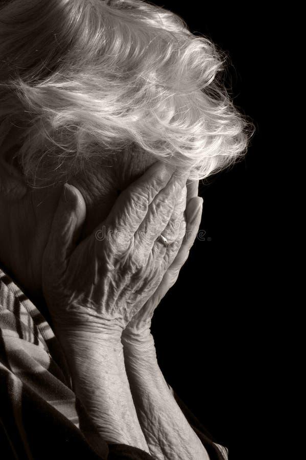 Las mujeres mayores tristes con sus manos a su cara son consternación imágenes de archivo libres de regalías