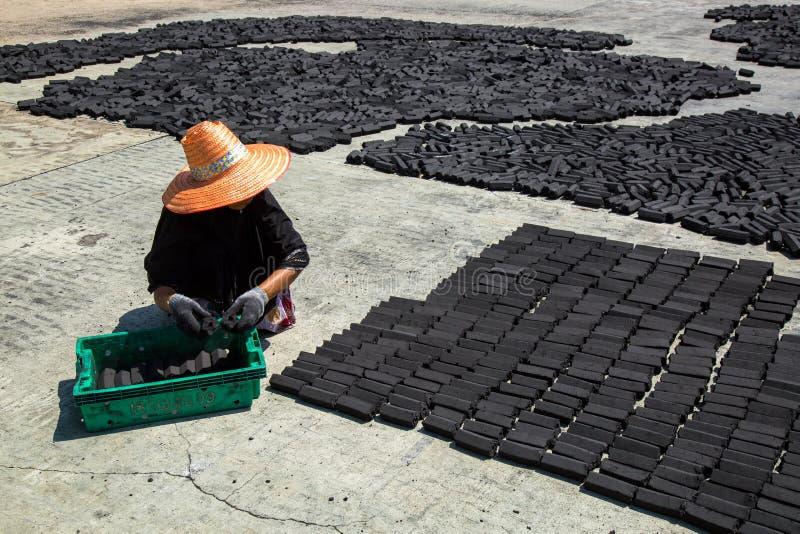 Las mujeres musulmanes pusieron la barra del paquete del carbón de leña hecha de cáscara del coco en el piso foto de archivo libre de regalías