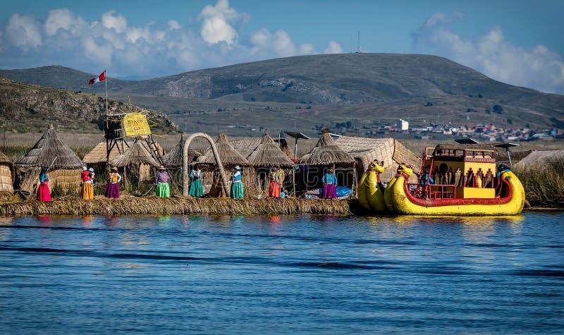 Las mujeres no identificadas acogen con satisfacción al turista en el lago Titicaca en Puno, foto de archivo libre de regalías