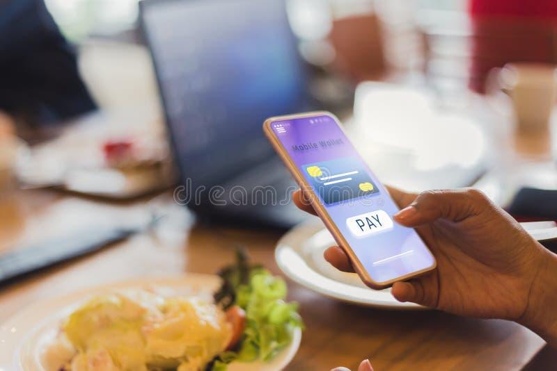 Las mujeres pagan la comida usando tarjetas de crédito a través de los teléfonos móviles en restaurantes imagenes de archivo