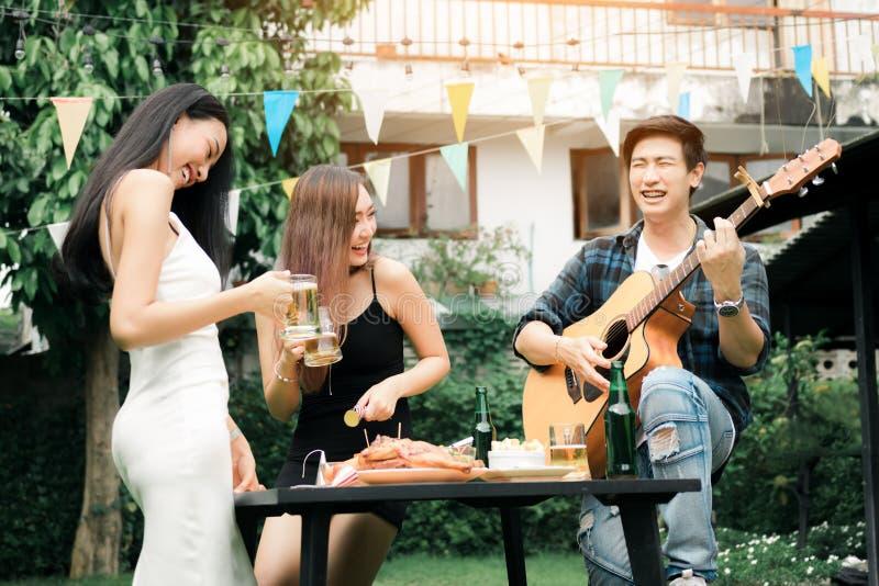 Las mujeres que disfrutan de bebidas van de fiesta con el individuo que toca la guitarra que canta en h imagenes de archivo