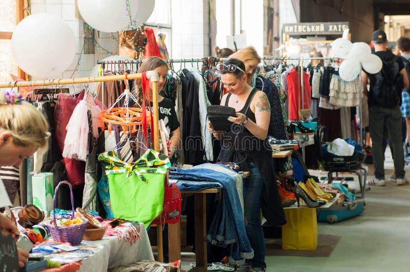 Las mujeres que hacen compras dentro del pasillo enorme del mercado del vintage visten imagen de archivo libre de regalías