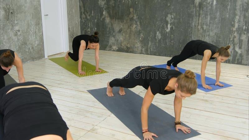Las mujeres que hacen el saludo del sol de la yoga presentan dentro en el estudio de la yoga foto de archivo