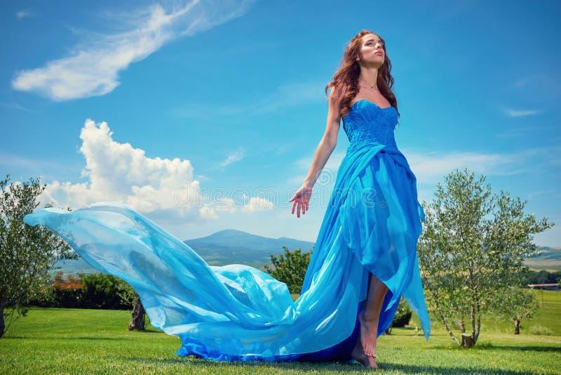 Las mujeres que llevan el vestido largo azul en la puesta del sol en Toscana colocan imágenes de archivo libres de regalías
