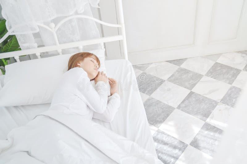 Las mujeres que llevan los pijamas blancos descansan sobre el colch?n imagen de archivo libre de regalías