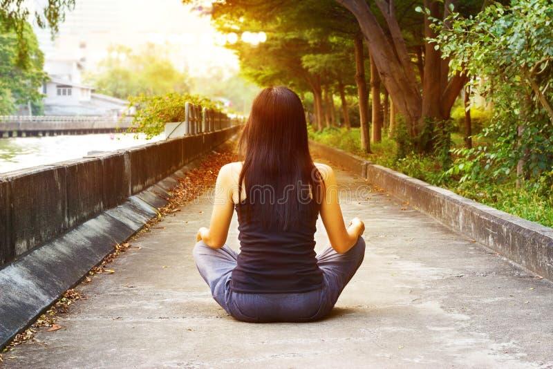 Las mujeres que meditan en calle parquean, tono caliente del color foto de archivo