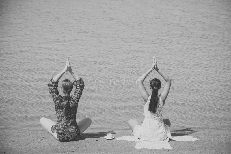 Las mujeres que meditan en yoga presentan con la taza de café en el agua foto de archivo