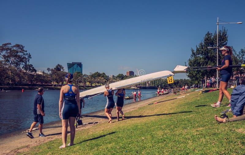 Las mujeres que reman al equipo se preparan para comenzar con su barco en el banco del río de Yarra fotografía de archivo