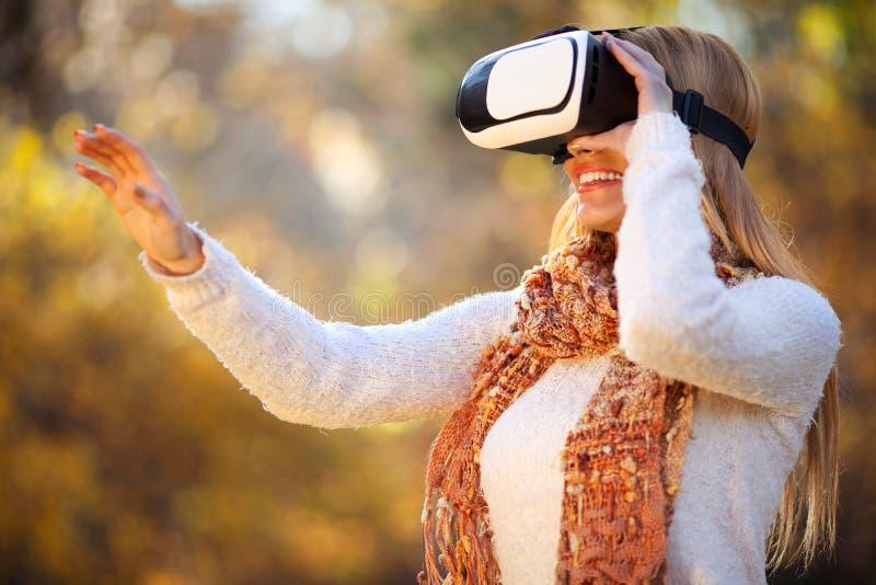 Las mujeres que usan los vidrios blancos de las auriculares de la realidad virtual en otoño parquean fotos de archivo