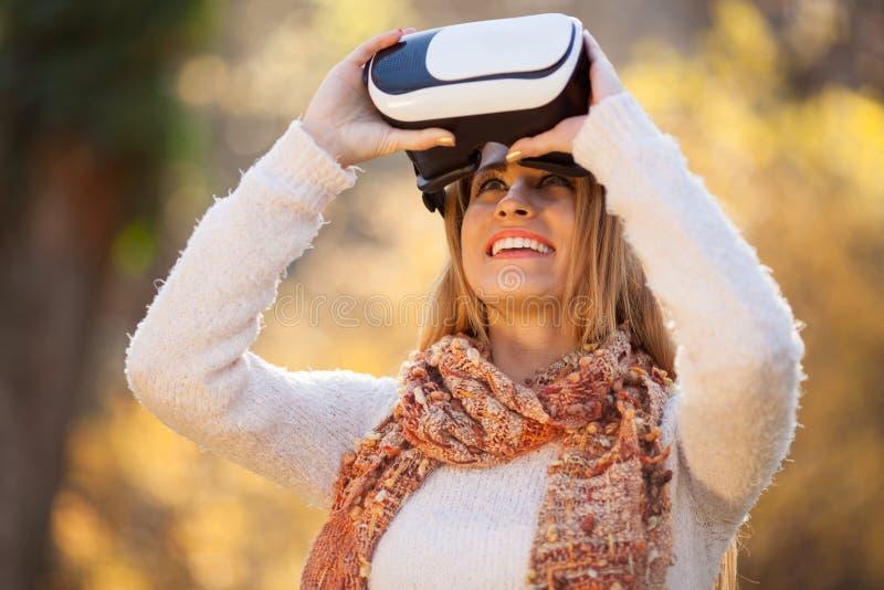 Las mujeres que usan los vidrios blancos de las auriculares de la realidad virtual en otoño parquean imágenes de archivo libres de regalías