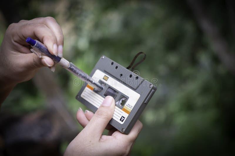 Las mujeres rebobinan un casete del acuerdo del vintage de la cinta de casete en el fondo de la falta de definición, cierre encim imagen de archivo