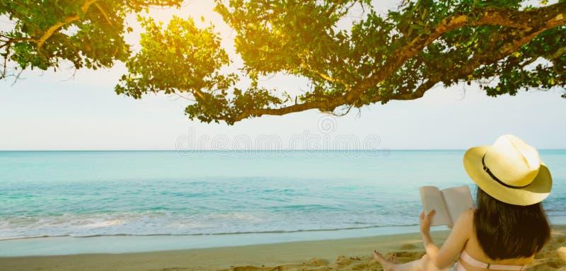Las mujeres se sientan y leyendo un libro debajo del árbol en la playa Opinión trasera la mujer asiática atractiva con el sombrer imagen de archivo