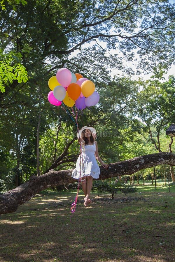 Las mujeres son sonrisa, sentándose sosteniendo una bola transparente debajo del árbol imagenes de archivo