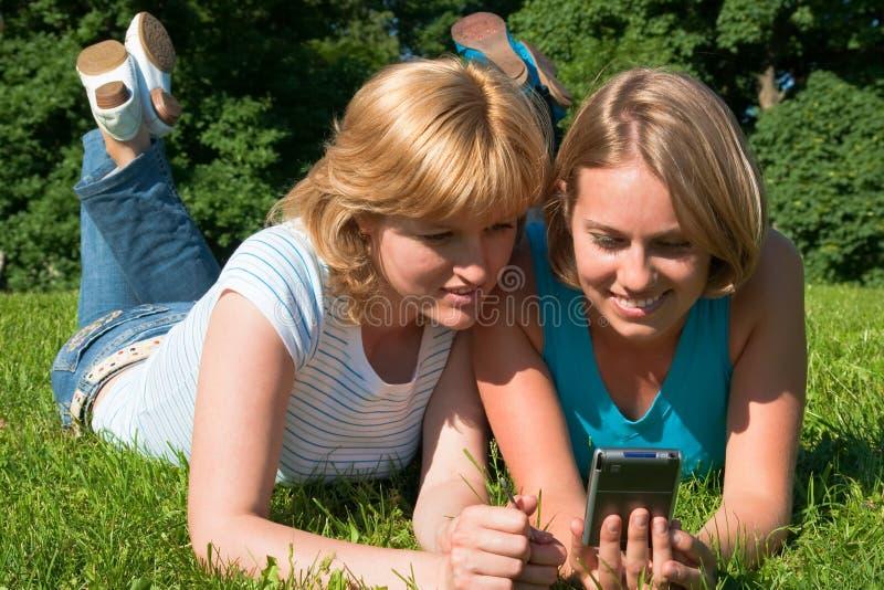 Las mujeres sostienen el ordenador del bolsillo foto de archivo