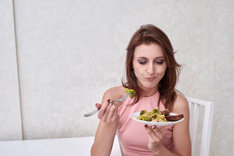 Las mujeres tristes están en el tiempo de dieta que mira el bróculi en la bifurcación la muchacha no quiere comer verduras y tene fotos de archivo