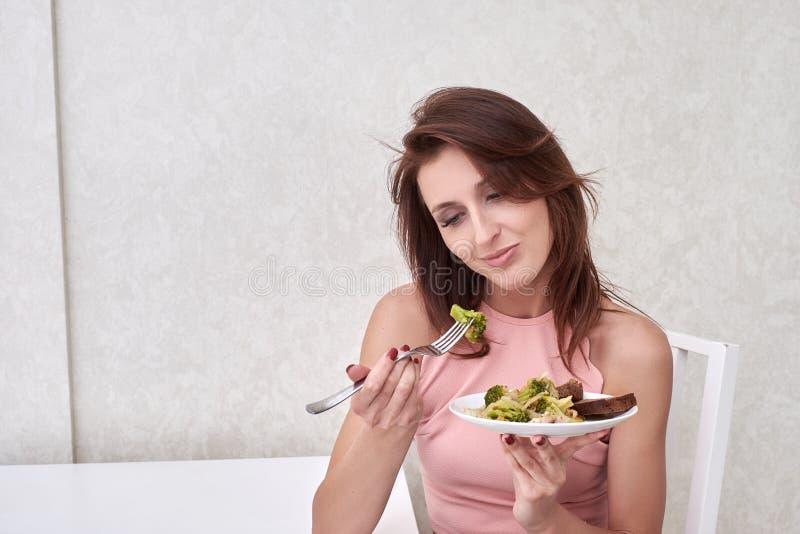 Las mujeres tristes están en el tiempo de dieta que mira el bróculi en la bifurcación la muchacha no quiere comer verduras y tene foto de archivo libre de regalías