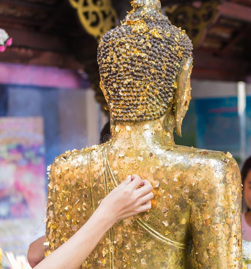 Las mujeres utilizan la hoja de oro en el Buda fotos de archivo