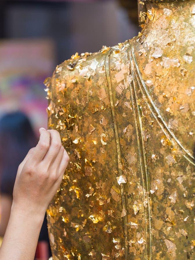 Las mujeres utilizan la hoja de oro en el Buda fotografía de archivo