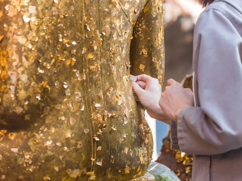 Las mujeres utilizan la hoja de oro en el Buda imagen de archivo libre de regalías