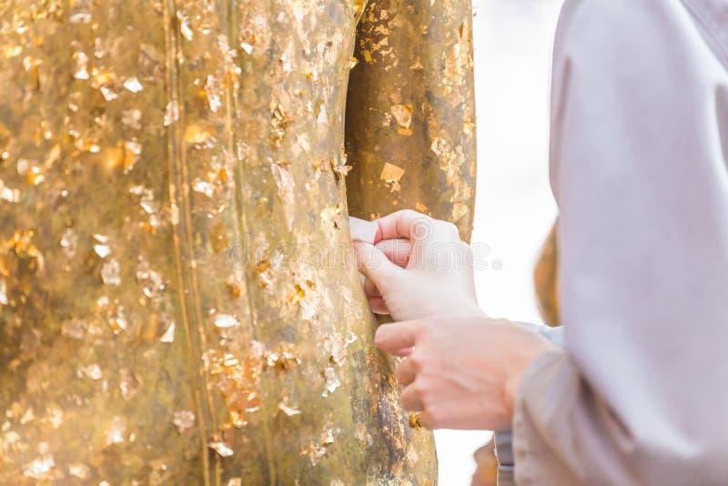 Las mujeres utilizan la hoja de oro en el Buda fotografía de archivo libre de regalías