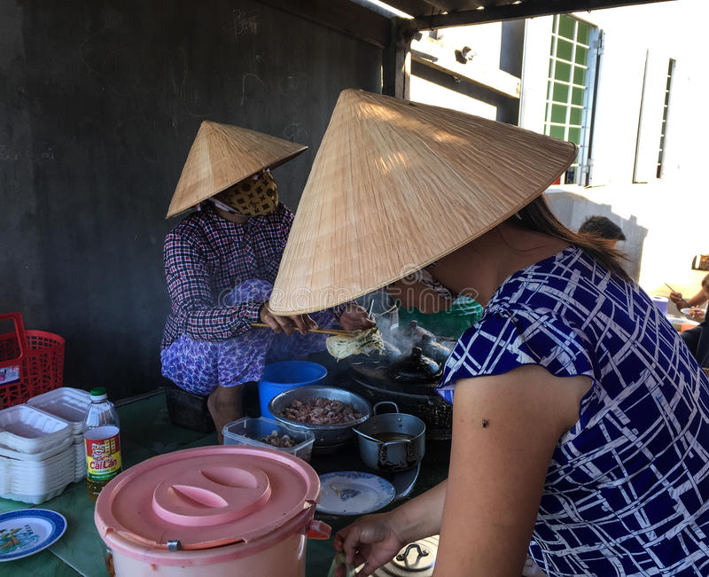 Las mujeres vietnamitas que vendían las comidas de la calle en Phan sonaron, Vietnam foto de archivo