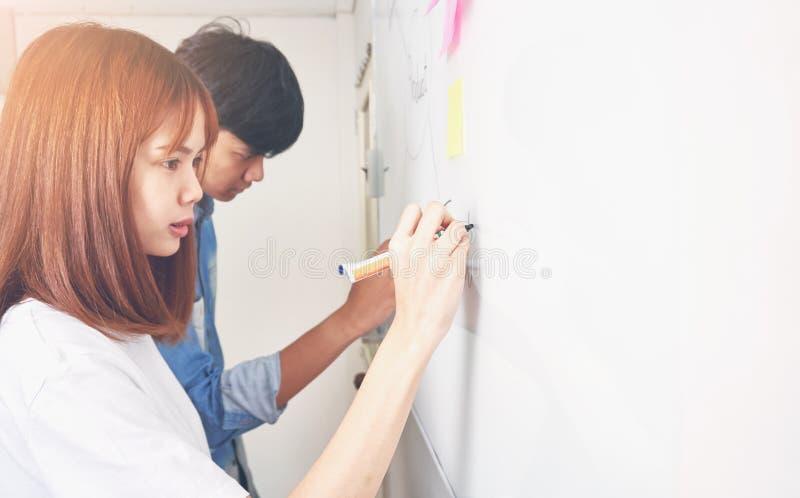 Las mujeres y el hombre de negocios están presentando un diagrama de funcionamiento a los clientes Para alcanzar la meta imágenes de archivo libres de regalías