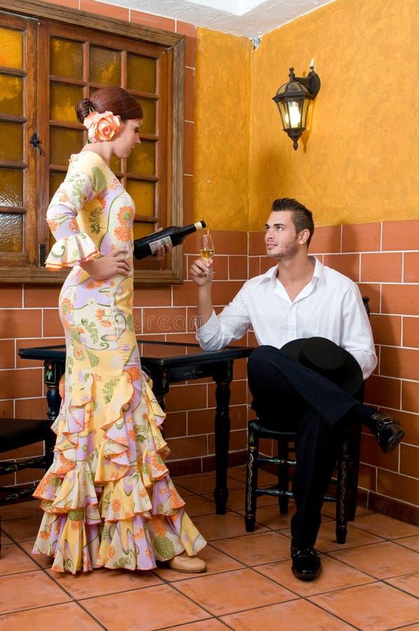 Las mujeres y el hombre en vestidos tradicionales del flamenco bailan durante Feria de Abril en April Spain fotografía de archivo
