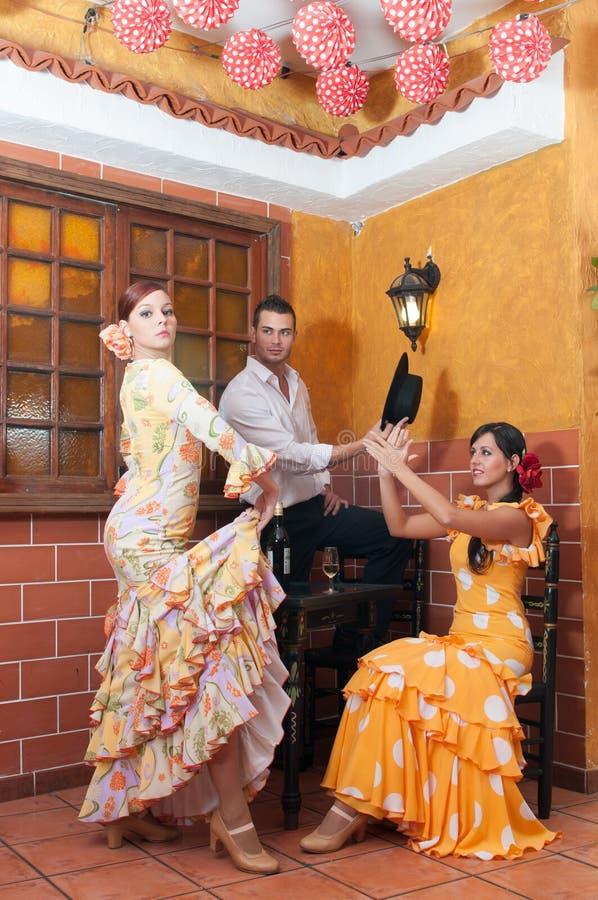 Las mujeres y el hombre en vestidos tradicionales del flamenco bailan durante Feria de Abril en April Spain imágenes de archivo libres de regalías