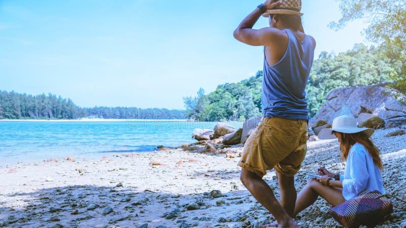 Las mujeres y los hombres asi?ticos de los pares del amante viajan naturaleza El viaje se relaja Agua de mar del juego en la play imagen de archivo libre de regalías