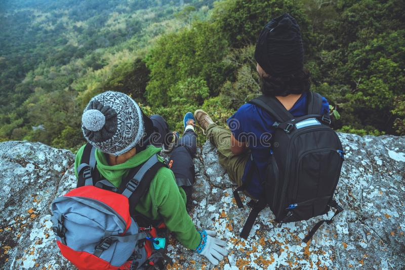 Las mujeres y los hombres asi?ticos del amante viajan naturaleza El viaje se relaja Siente y mire el Mountain View En un acantila imagen de archivo