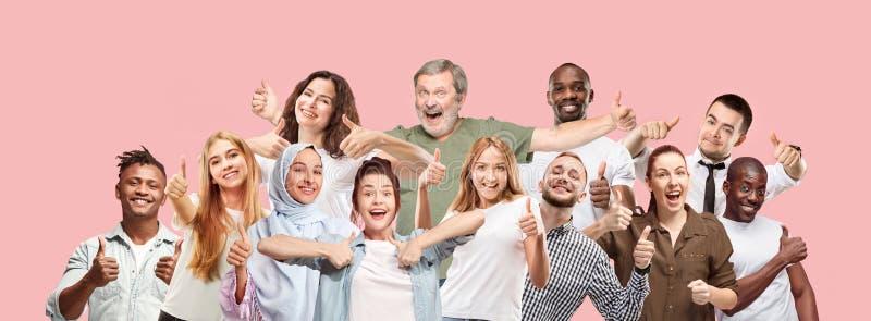 Las mujeres y los hombres felices de negocios que se oponen y que sonríen contra fondo rosado imagenes de archivo
