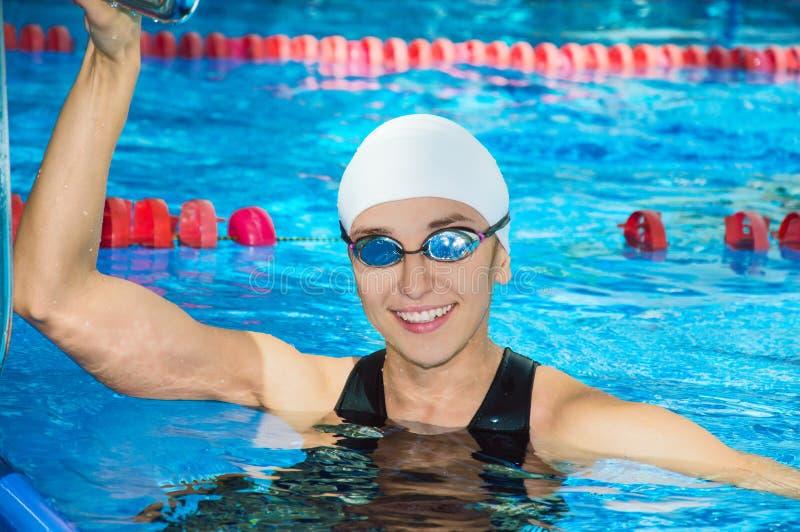Las nadadas encantadoras de la muchacha al lado de la piscina miran la cámara imágenes de archivo libres de regalías
