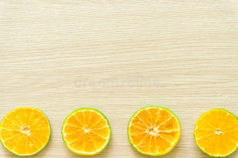 Las naranjas cortaron por la mitad en un fondo de madera, espacio libre imagen de archivo
