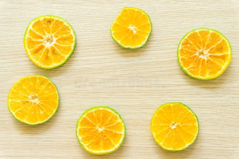 Las naranjas cortaron por la mitad en un fondo de madera, espacio libre fotos de archivo
