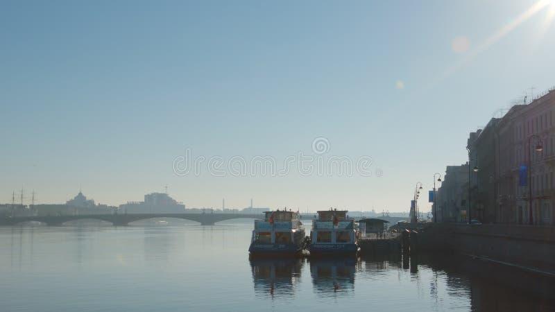 Las naves del viaje se colocan cerca de un terraplén del río de Neva en madrugada foto de archivo