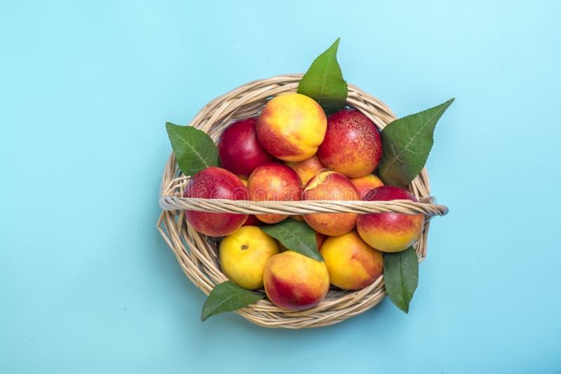 Las nectarinas cosechadas frescas, placa, dejan mentiras redondas en el melocotón natural del fondo de las verduras de la querati imagen de archivo libre de regalías