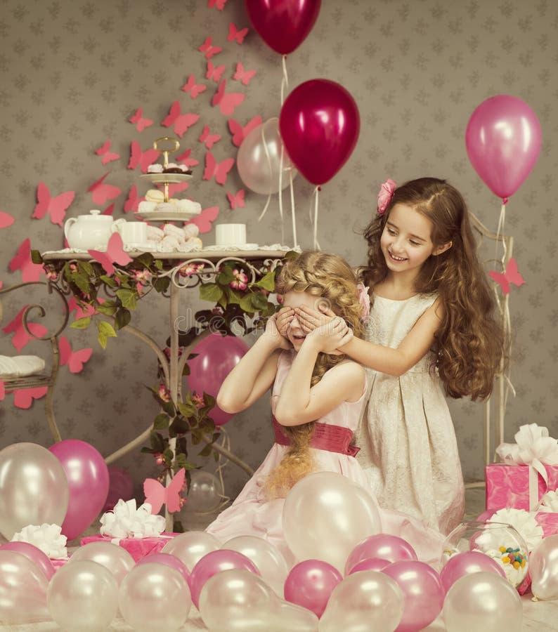 Las niñas de los niños que cubren los ojos, cumpleaños de los niños, presentan los globos imagen de archivo libre de regalías