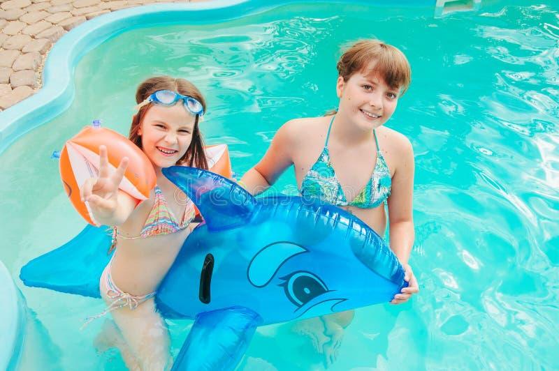 Las niñas están nadando en la piscina por un día de verano imagen de archivo libre de regalías