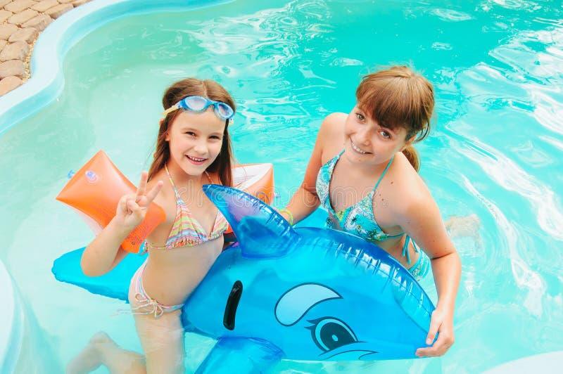 Las niñas están nadando en la piscina por un día de verano imagenes de archivo