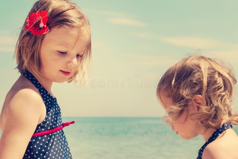 Las niñas hermosas (hermanas) juegan en el mar fotos de archivo libres de regalías