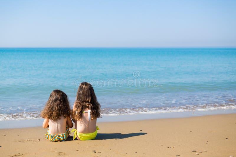 Las niñas se sientan cómodamente en la arena y la mirada en el mar Concepto de las vacaciones de familia Hermanas felices Copie e fotografía de archivo libre de regalías
