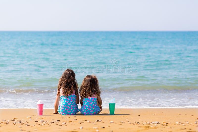 Las niñas se sientan cómodamente en la arena y la mirada en el mar Concepto de las vacaciones de familia Hermanas felices Copie e imagenes de archivo