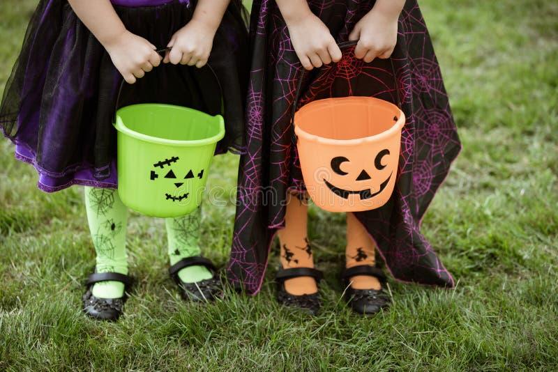 Las niñas sostienen cubos anaranjados y verdes del caramelo del truco o de la invitación de la linterna del enchufe o imagen de archivo